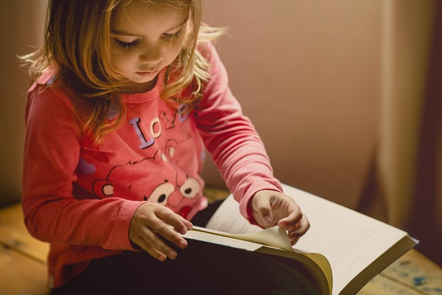 An image of a young girl reading book