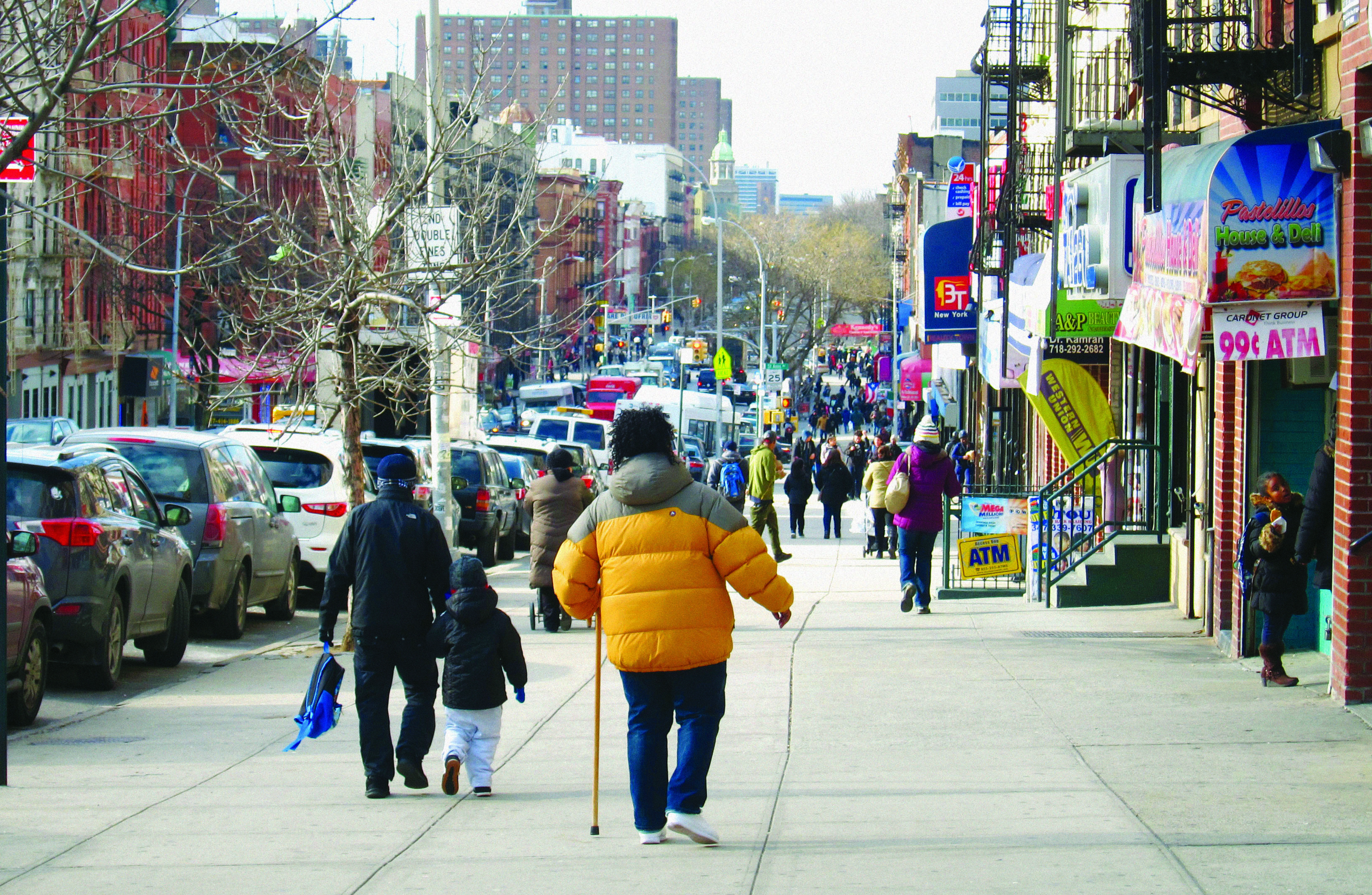 Man with a cane and in a yellow puffer jacket, walking down a busy East 138th Street