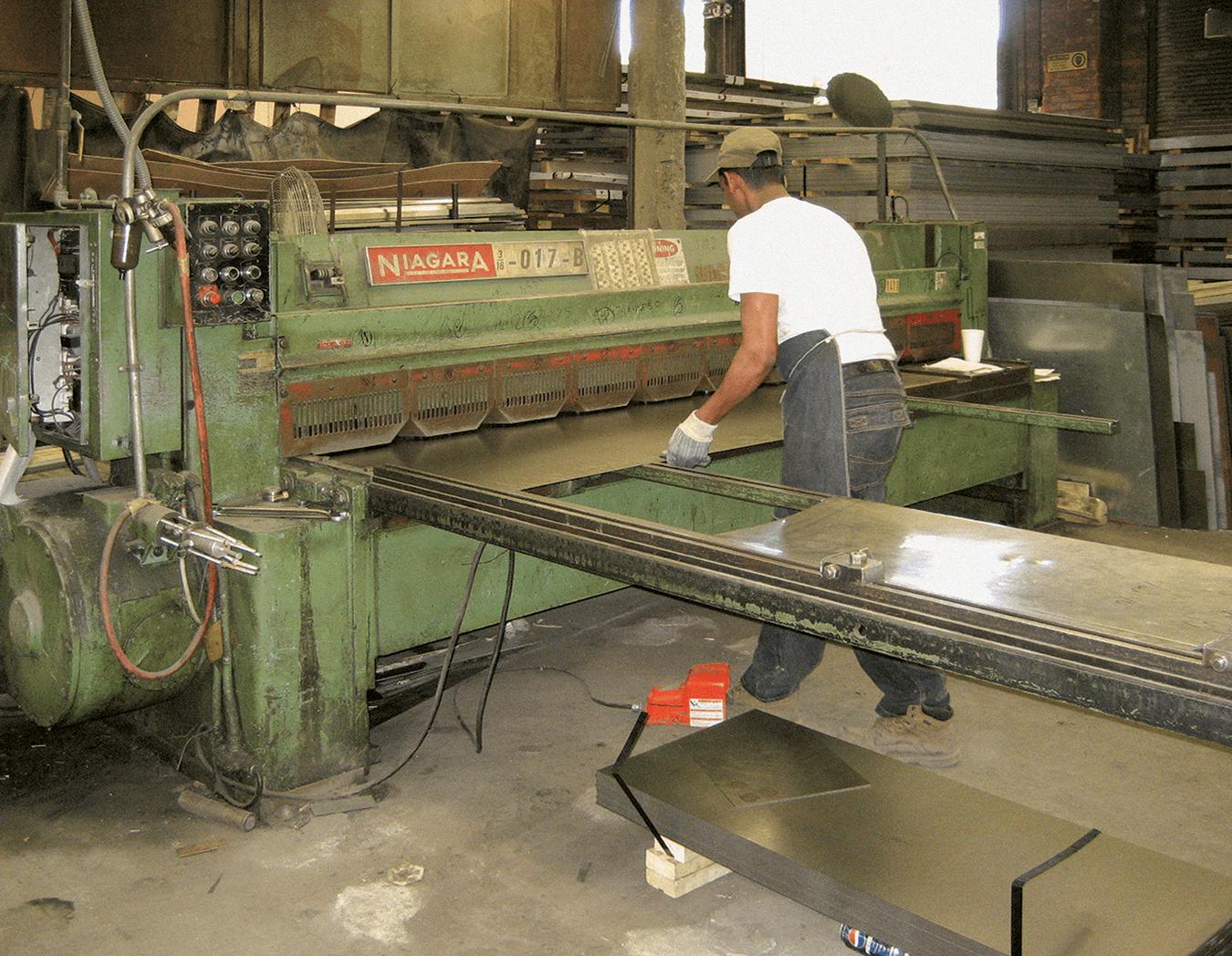 Man working, using a metal stamping machine.