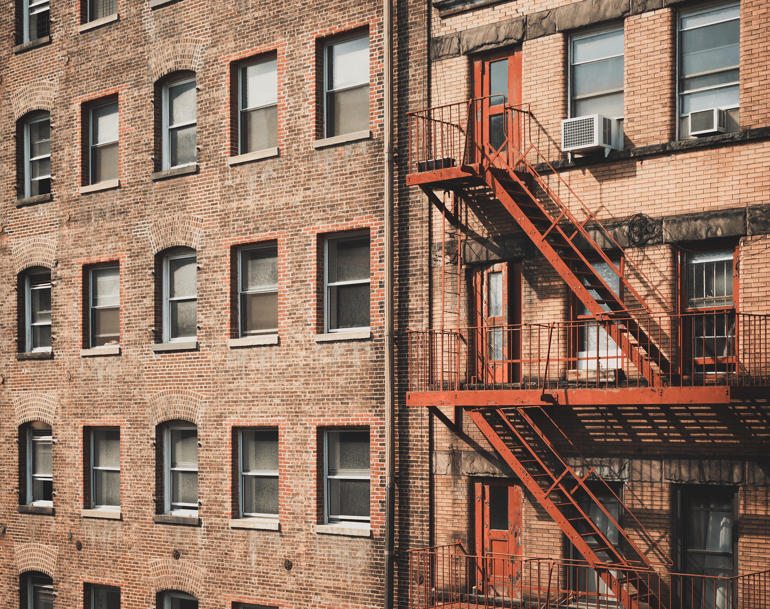 Side of urban building with red fire escape