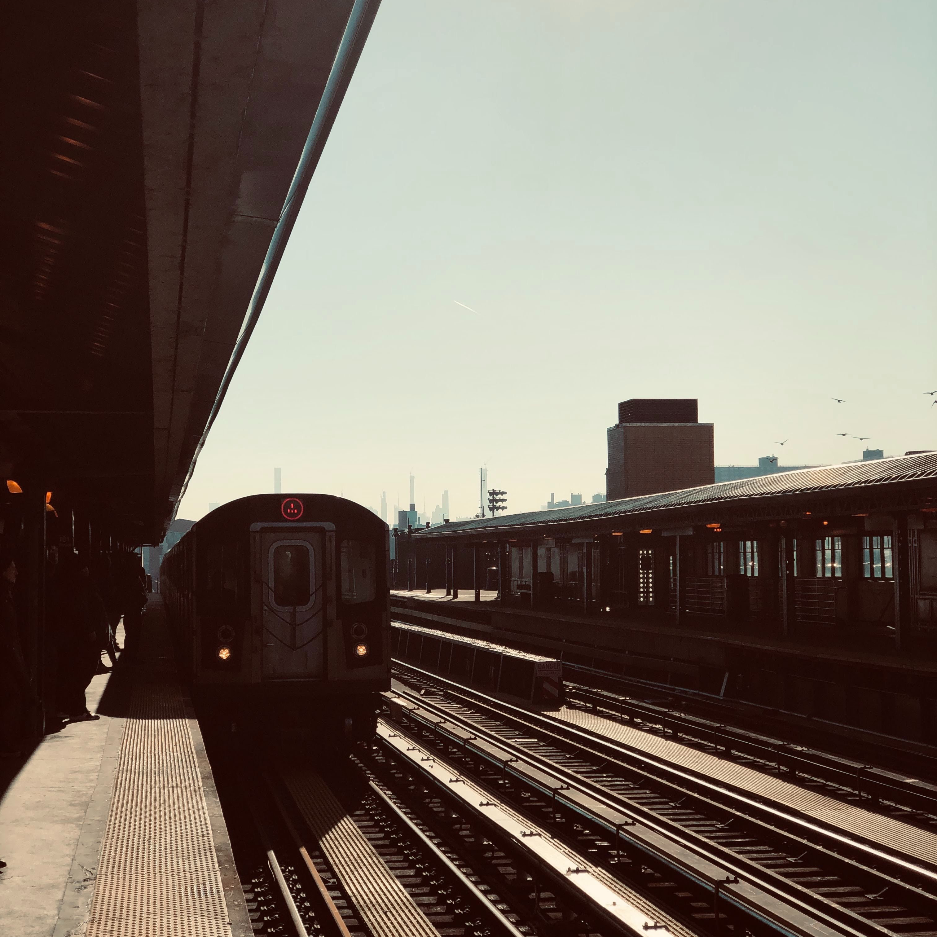 New York City Train pulling into the train station on an above ground platform in The Bronx
