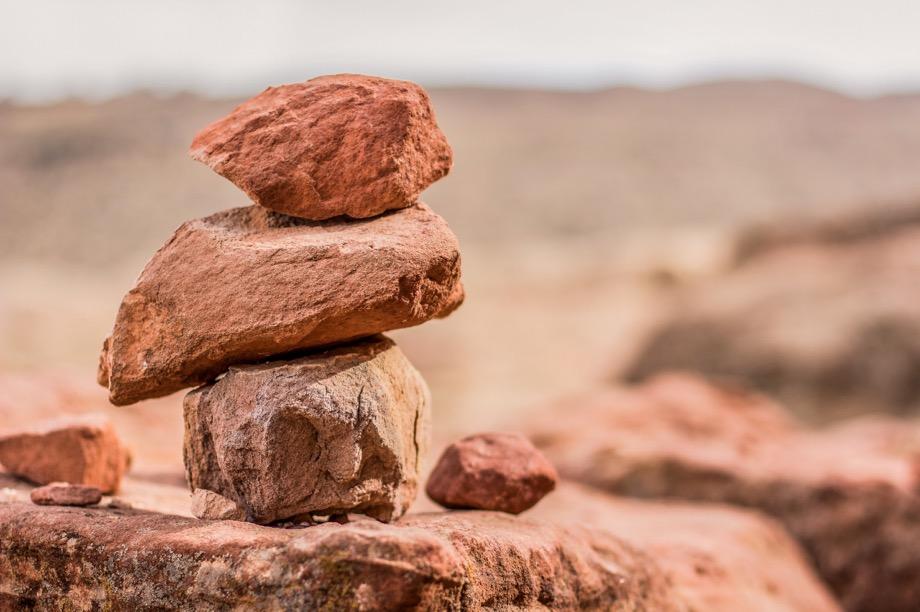 Three stacked, reddish desert rocks