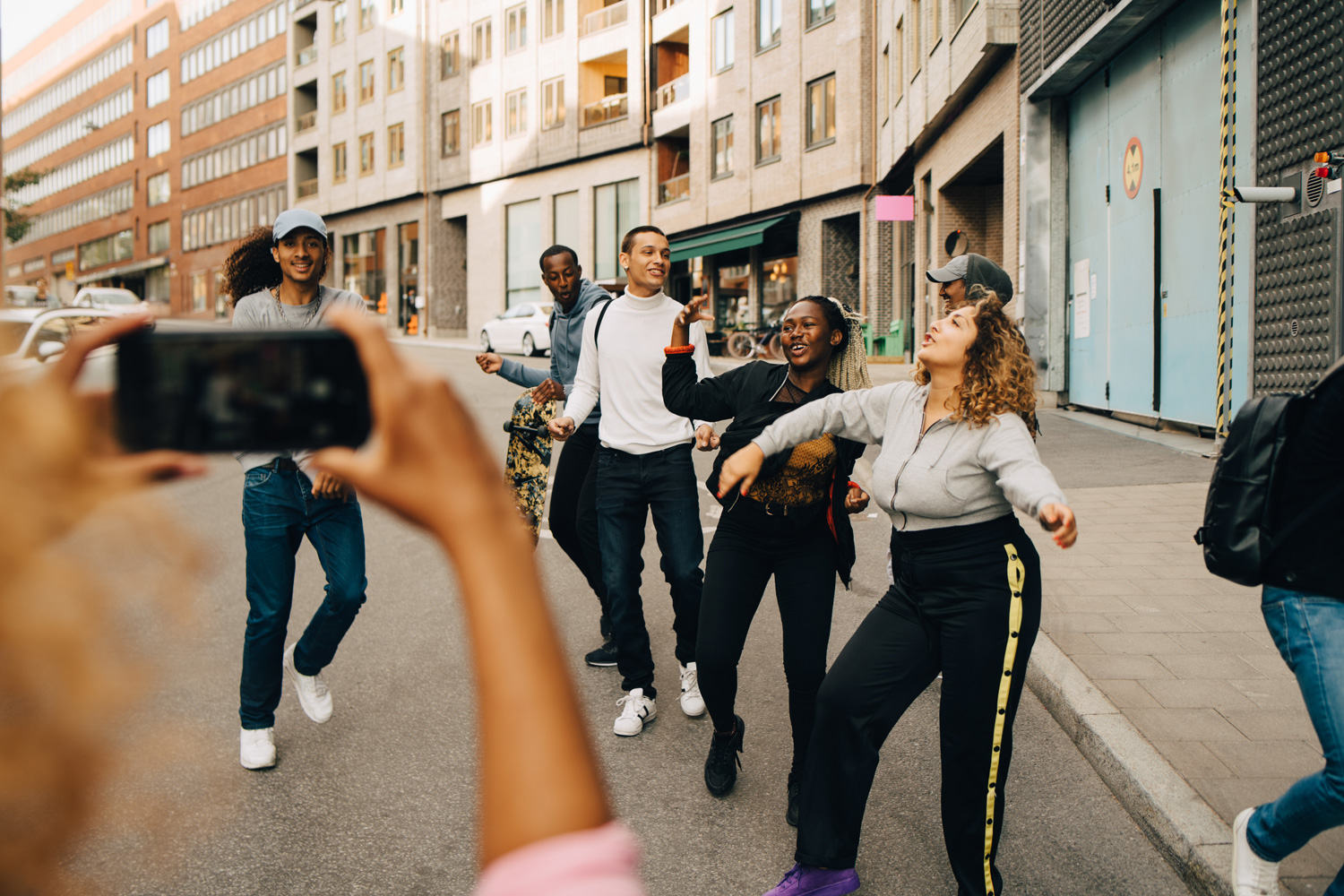 A group of people dancing together in the street as people film with their phones.