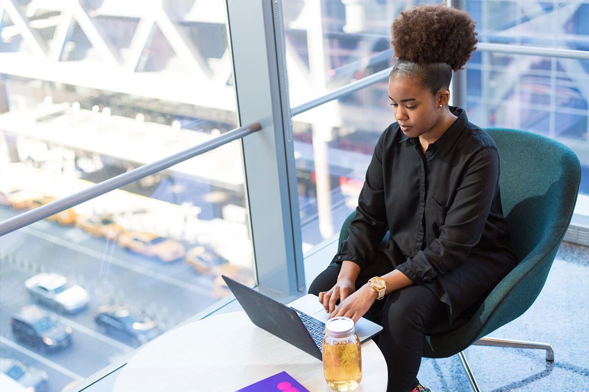 Woman of color in black dress using laptop by window.