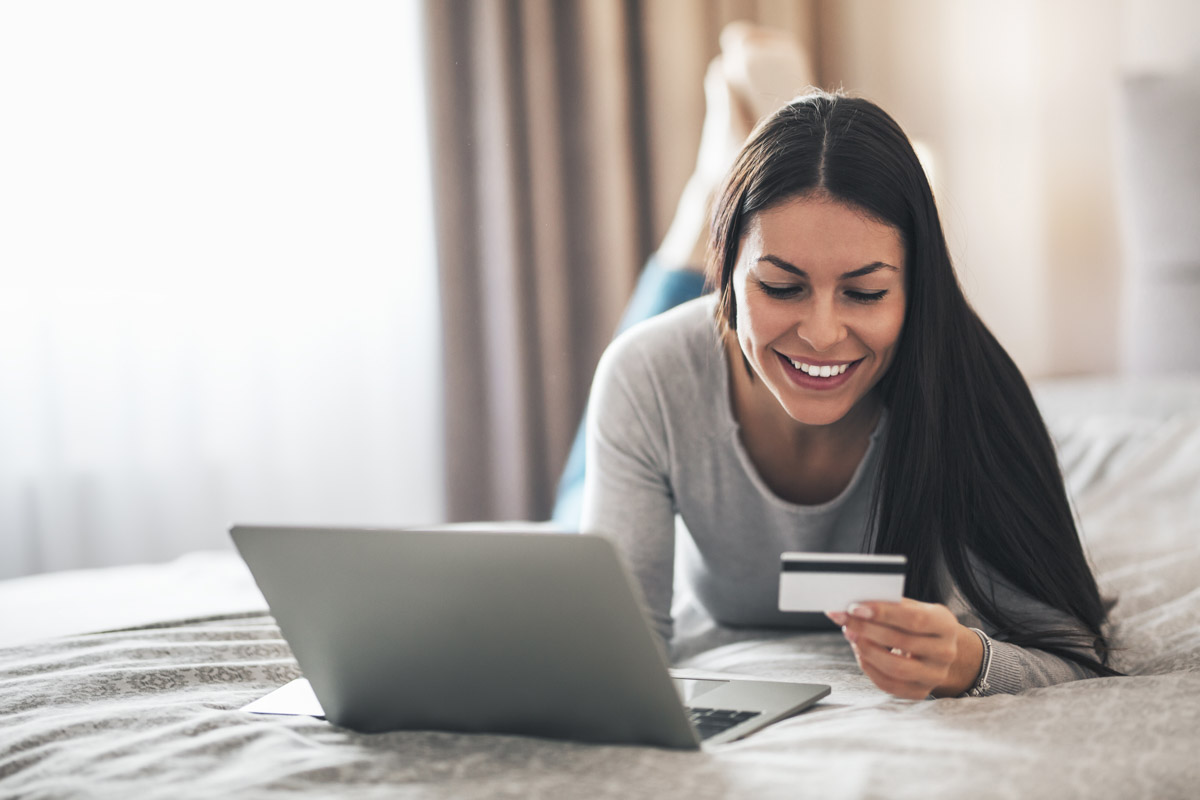 woman smiling as she looks at her credit card next to her computer
