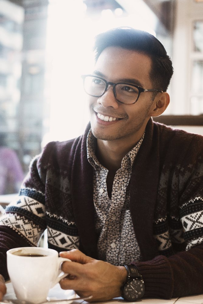 a man smiling with a cup of coffee