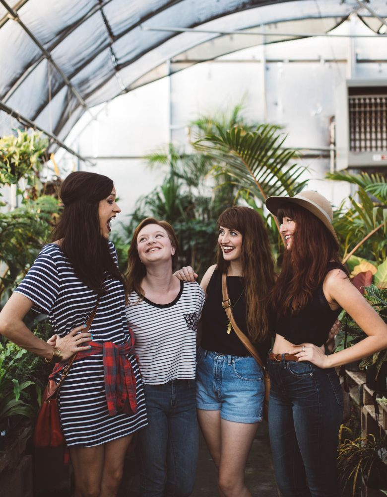 friends smiling at each other surrounded by plants