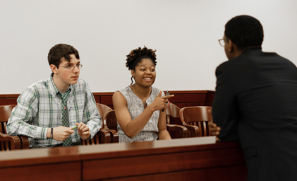 Image of Mutaqee instructing two volunteer participants, one male one female,  during a mock trial event.