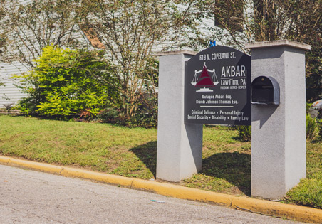 A photo of the sign outside of Akbar Law Firm's office.