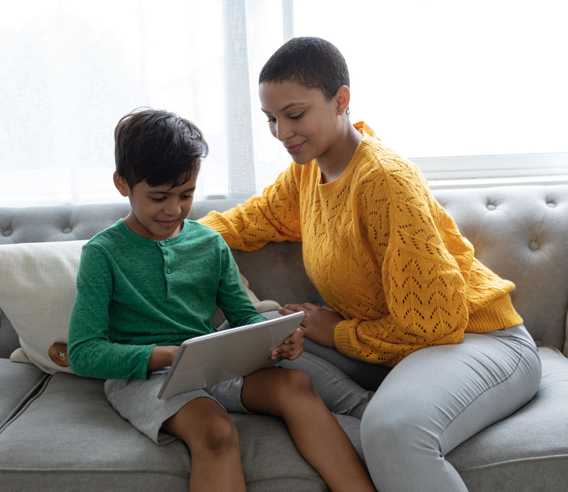 A Mother helping her child with a tablet, both sitting on a sofa