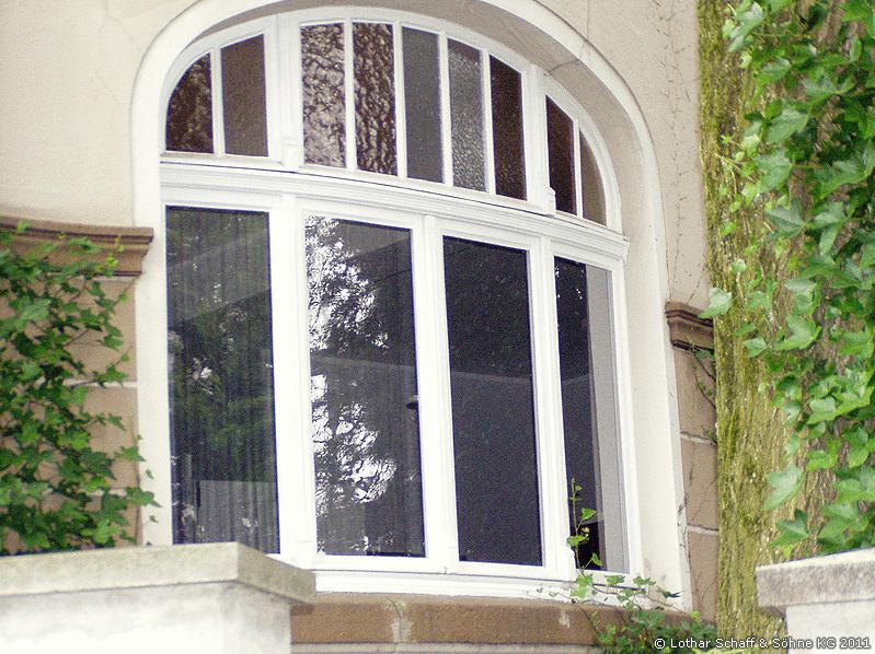 Altes Korbbogenfenster mit verschiedenen Gläsern