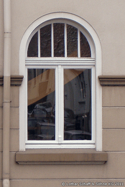 Altes Rundbogenfenster mit verschiedenen Glasarten