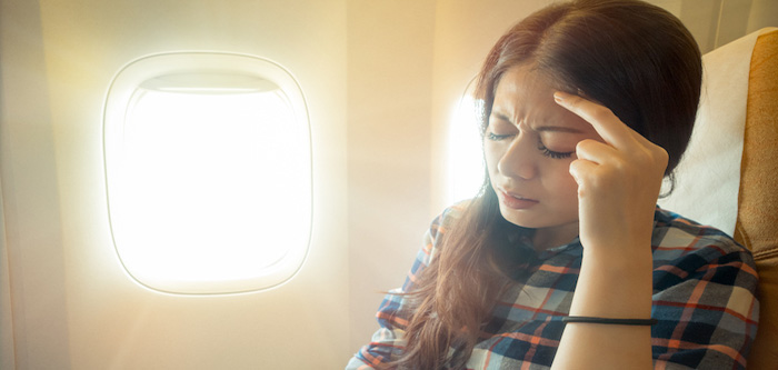 woman with sinus pain sitting on an airplane