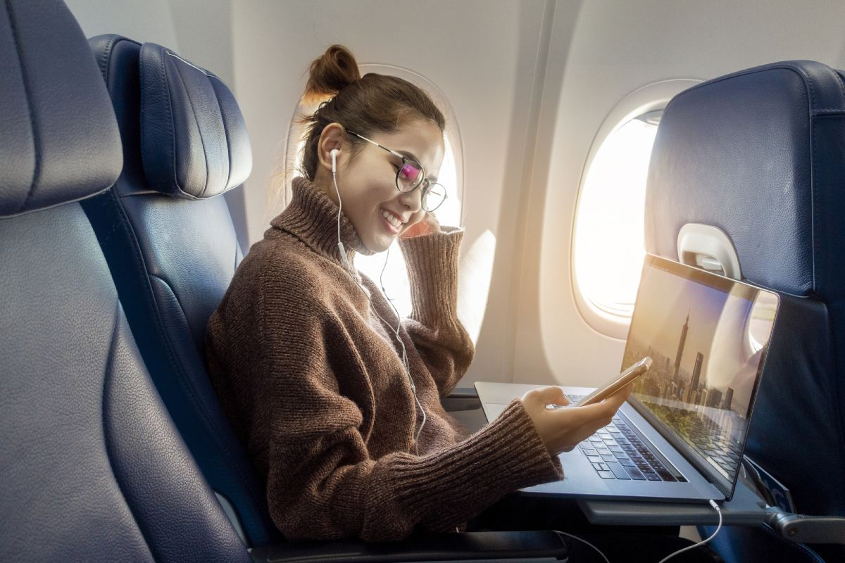 Woman working on a plane during a business travel trip