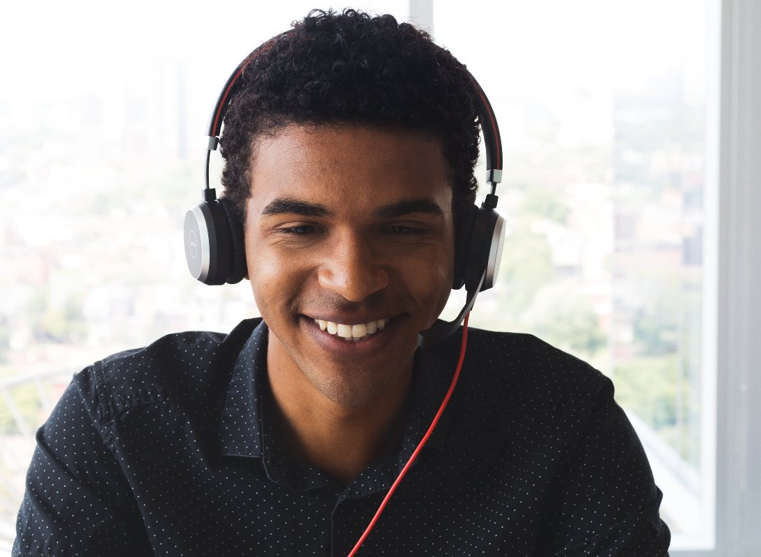 A man looking at his computer with headphones smiling