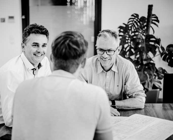 3 Männer sitzen lachend an einem Tisch.