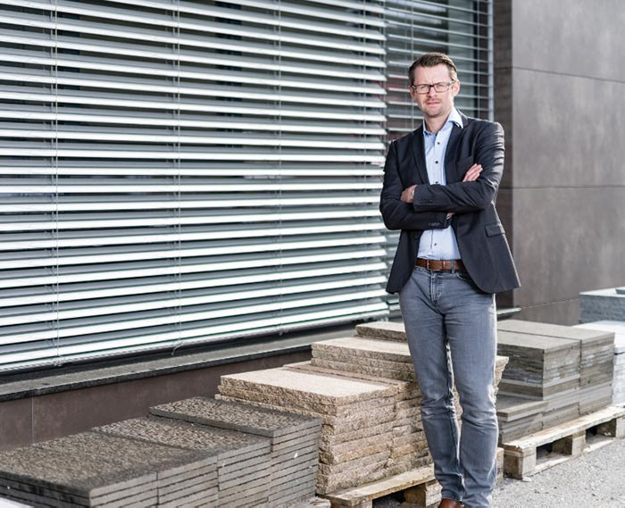 Ein Mann in einem Anzug steht vor einem modernen Gebäude.