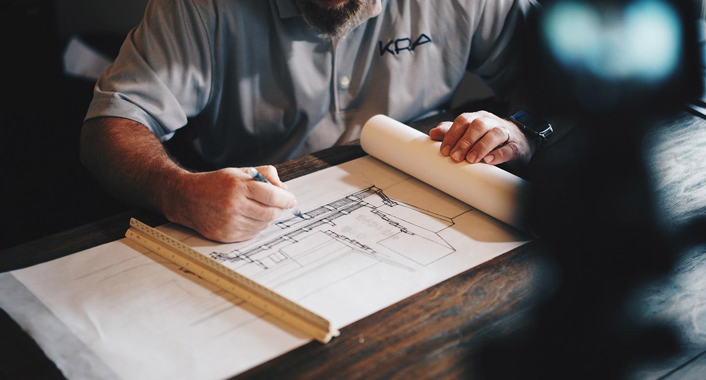 Eine Hand erstellt eine Skizze eines Gebäudes auf hellbraunem Papier.