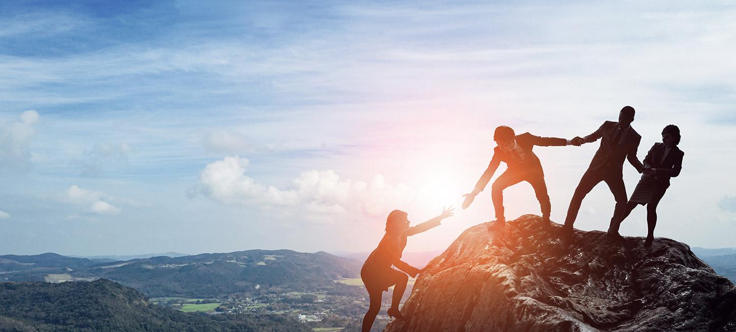 3 Personen stehen geschäftlich gekleiidet auf einem Berg und ziehen eine weitere hinauf.