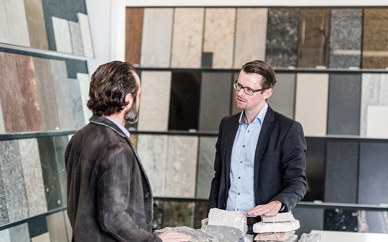 2 Männer stehen vor verschiedenen Fliessen und besprechen etwas.