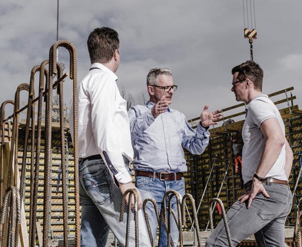 3 Männer stehen in einem Feld und besprechen etwas.