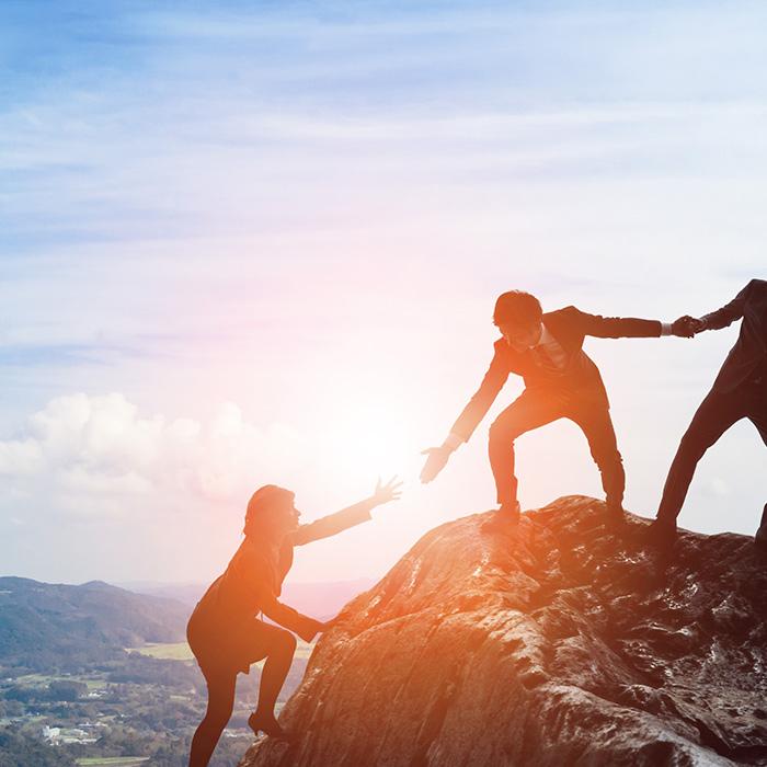 3 Personen stehen geschäftlich gekleidet auf einem Berg und ziehen eine weitere hinauf.
