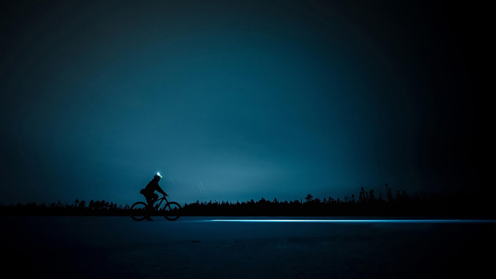 A man is riding a bike during night