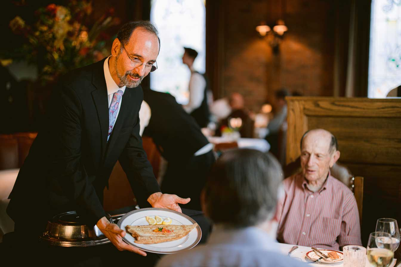 refectory owner Kamal Boulos serving a platter to a table of guests