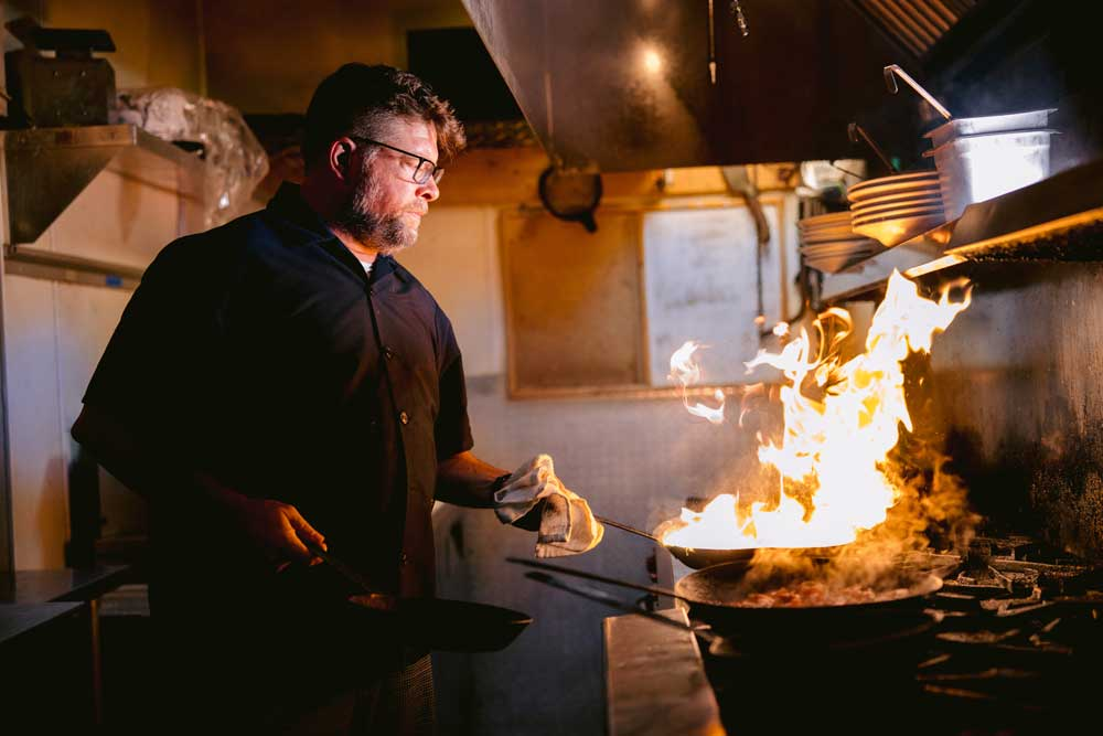 gmichaels columbus ohio head chef tossing a dish on the stove that temporarily flares up creating a flame