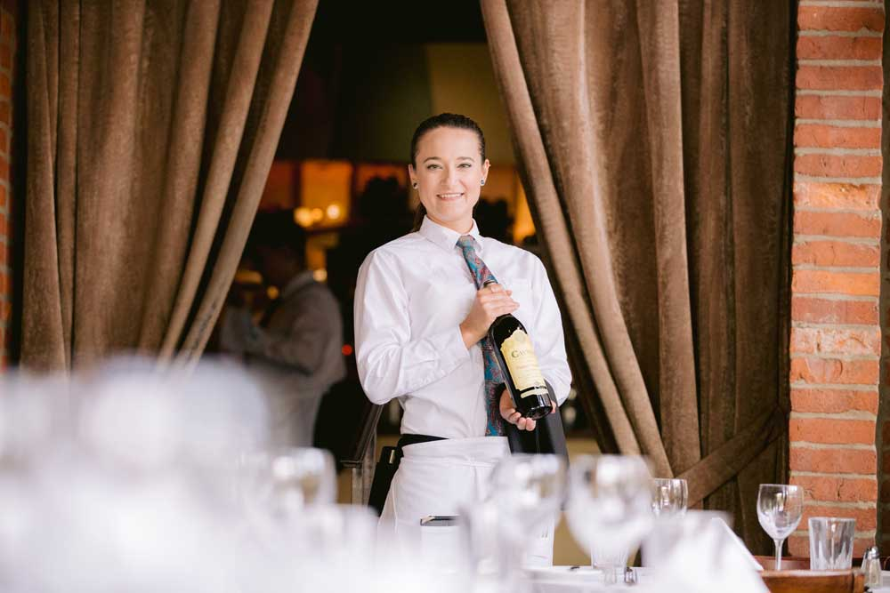 smiling server holding bottle of wine from gmichaels restaurant columbus ohio