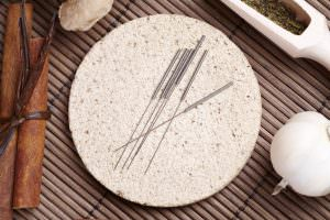 Acupuncture needles laying on the stone mat