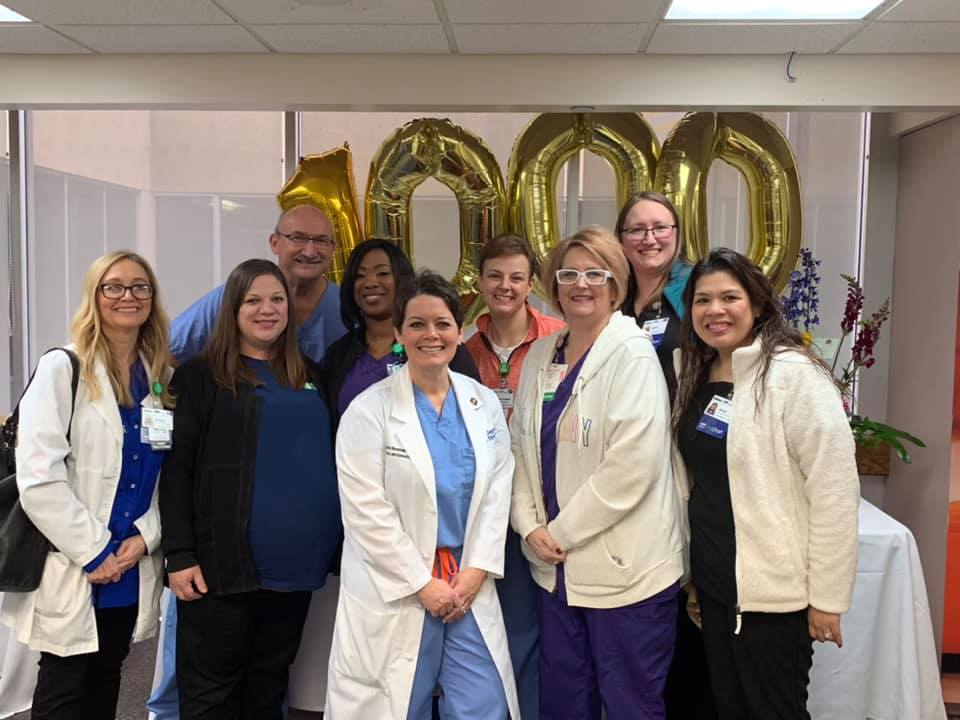 A group of male and female Baptist Health career professionals celebrating 1000 years.