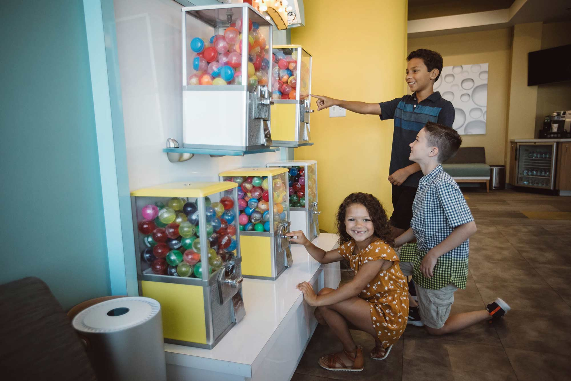 A photo of three children choosing prizes from our price machines.