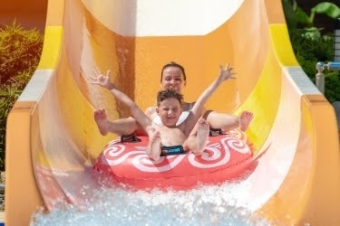 Woman and kid playing in the water slide.