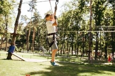 Boy zip lining in a park