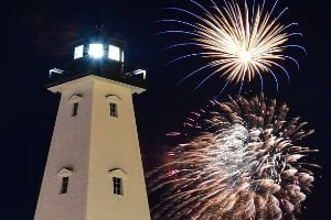 Gulfport Harbor's Lighthouse at night with fireworks in the back