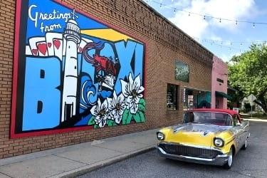 Yellow car next to a Biloxi Mural