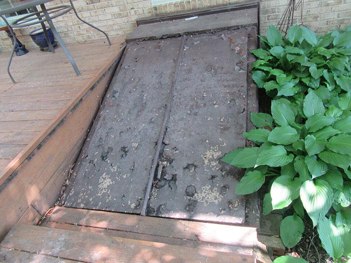 Rusted basement door before Vinyl Window Wells vinyl stairwell cover install