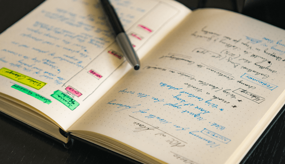 Close-up of an open notebook with very neat writing and highlighted text
