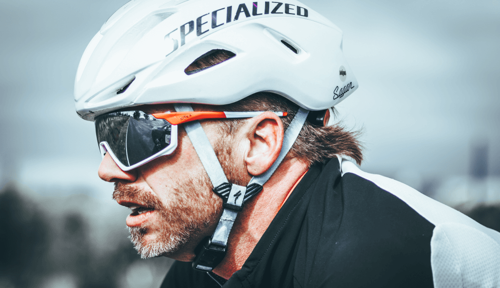 Close-up profile of a cyclist wearing a white helmet while riding a bike