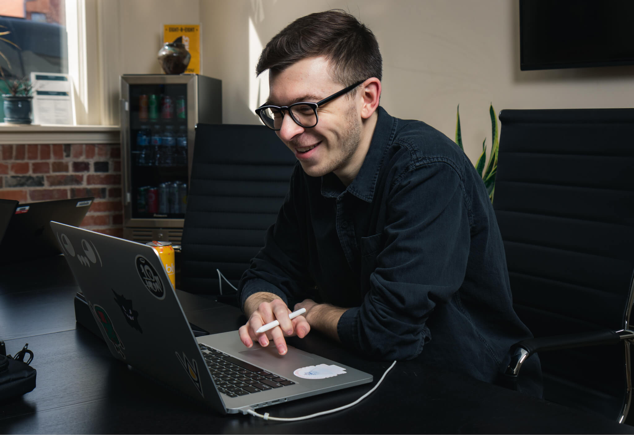 Designer sitting at a desk looking at a laptop