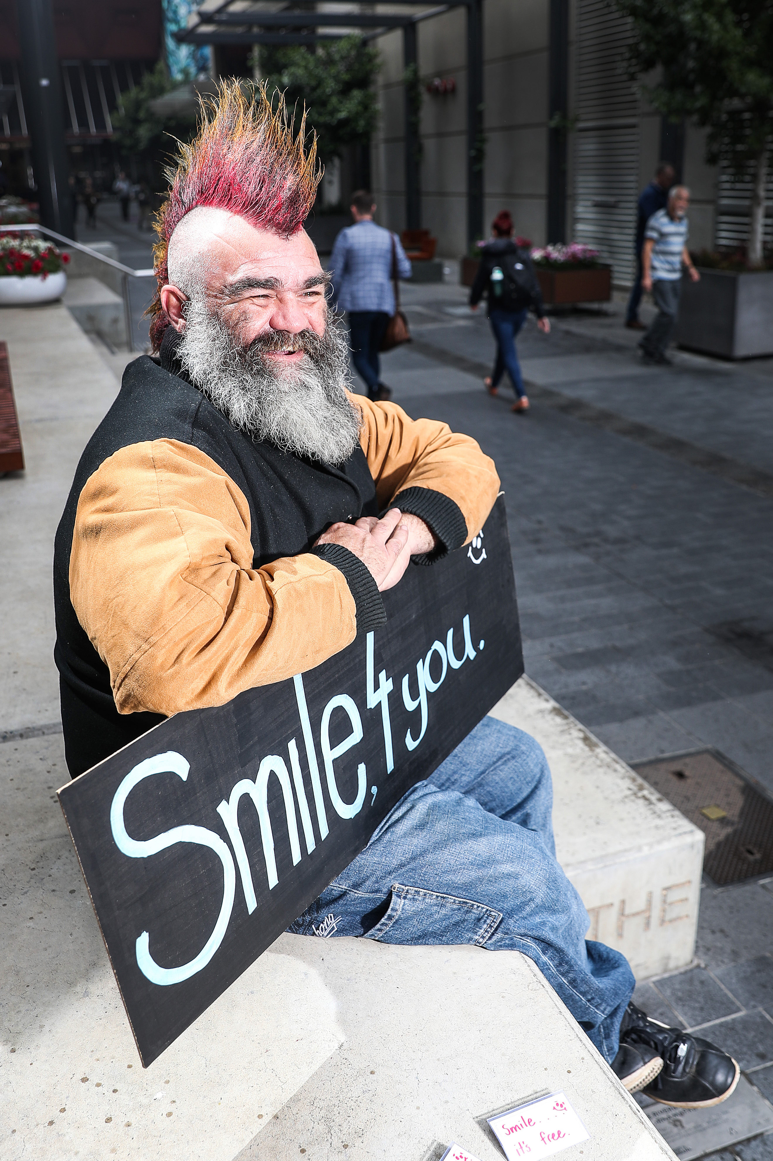 Stephen sits with his smile sign in the Adelaide CBD