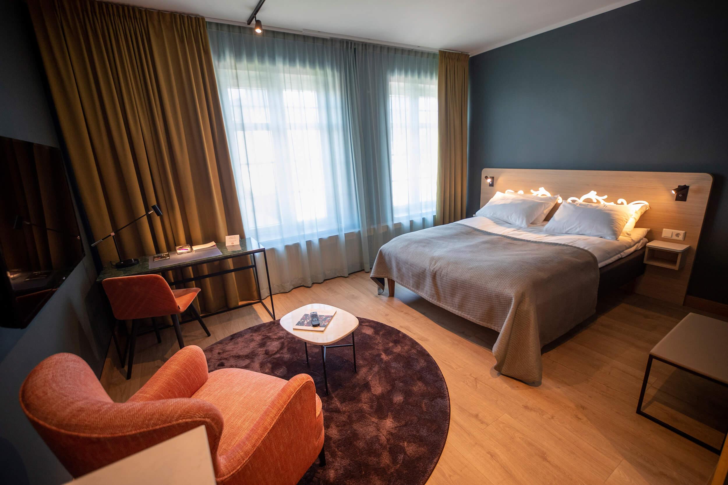 Hotellrom med dobbelseng, bord og stoler