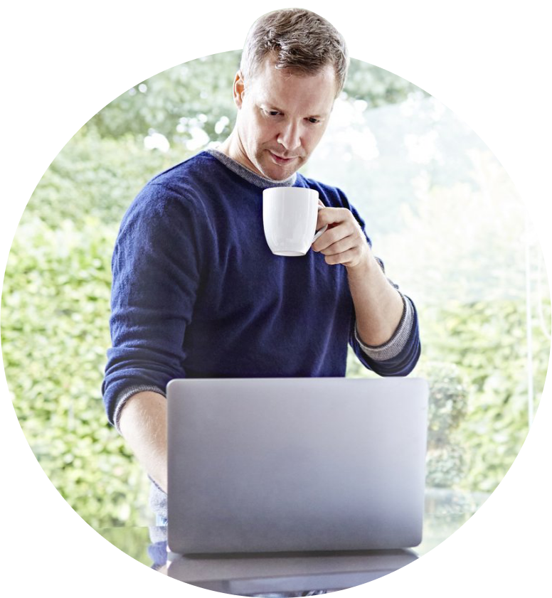 Man with mug on his laptop