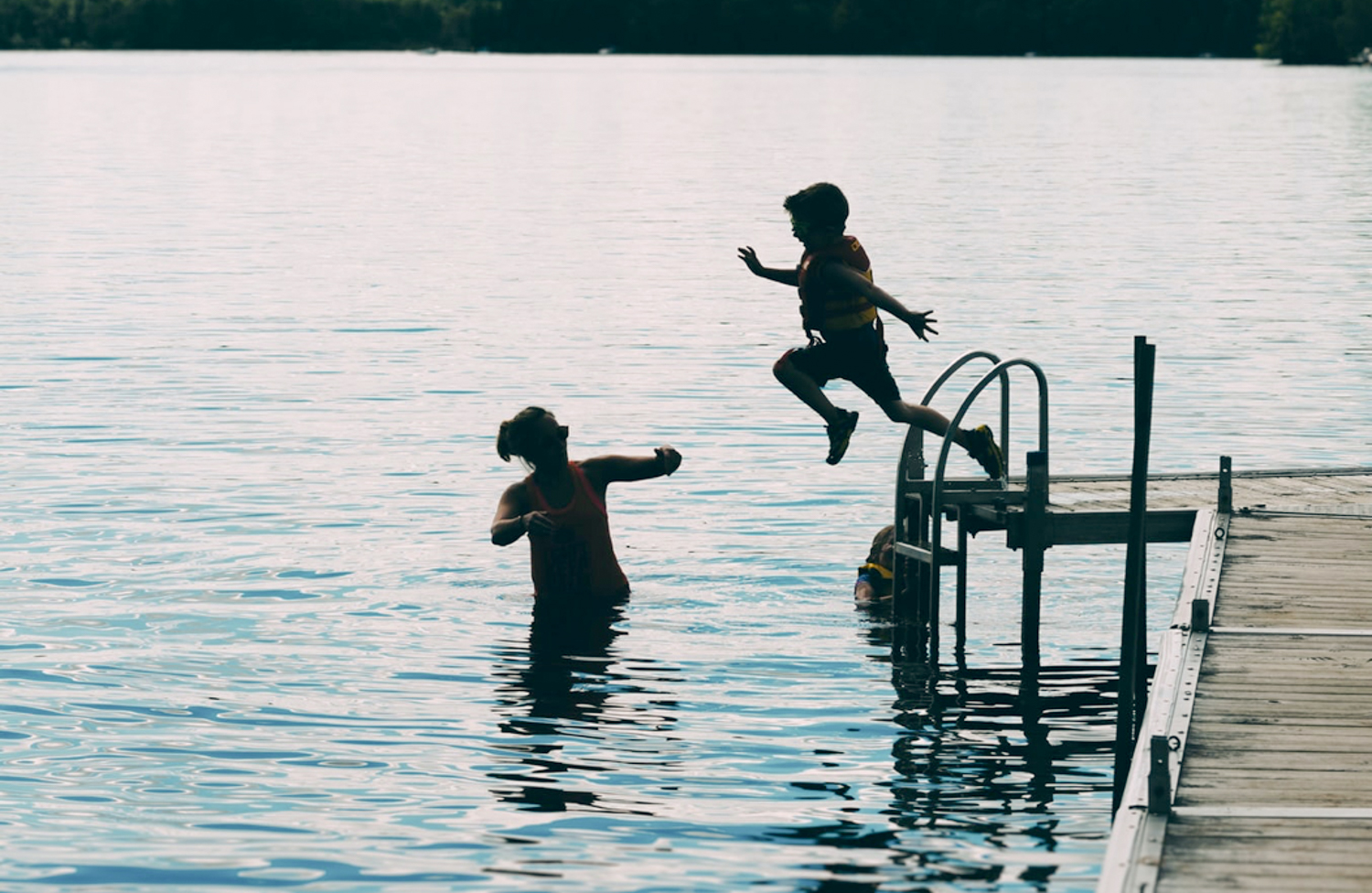 A Young Boy Jumping in a Lake
