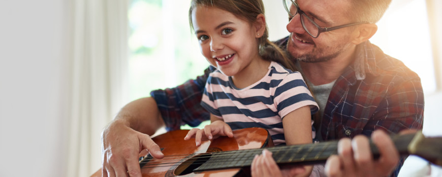 Little Girl Playing Guitar with Father