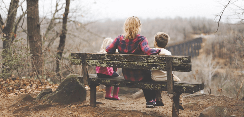 Mother with Two Kids Sitting on a Bench in the Park