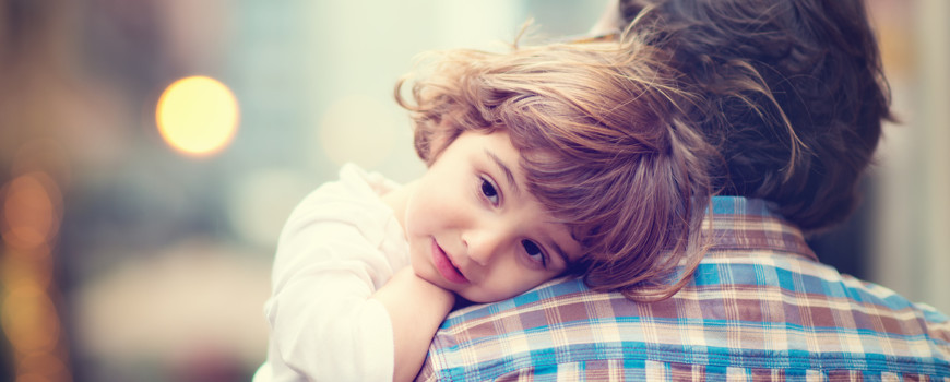 Little girl resting her head on her father's shoulder