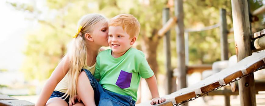 A little girl kissing a boy on the cheek