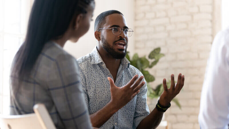 Man sharing New Years Resolutions with Support Group